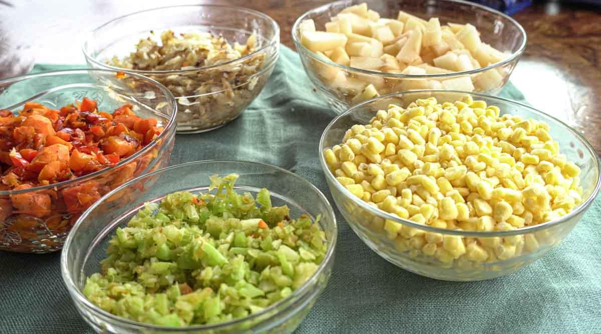 bowls of chopped celery, onions, carrots, potatoes, corn.