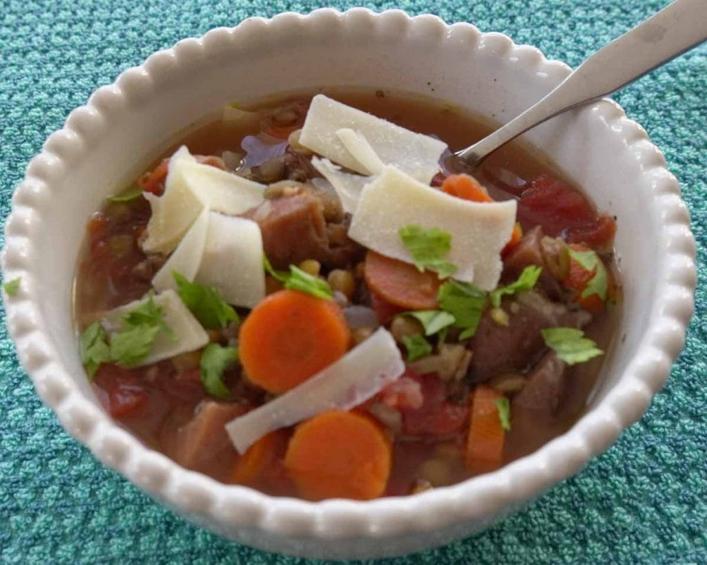 ham and lentil soup in white bowl