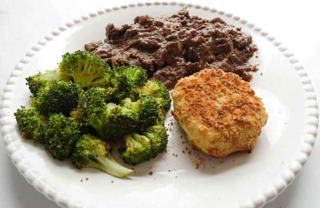 Slowcooker Sauerbraten, baked potato balls and broccoli on white plate