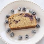 slice of blueberry swirl cake with sugared blueberries on white plate