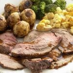 roast beef with gravy, broccoli, cauliflower on white plate