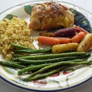 low carb sweet garlic chicken with riced cauliflower, string beans and carrots on dinner plate