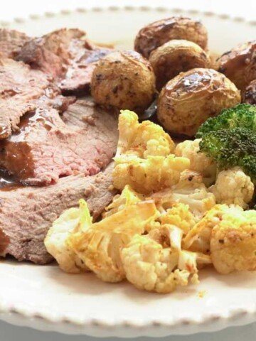 Garlic Roast Beef with roasted vegetables on white dinner plate
