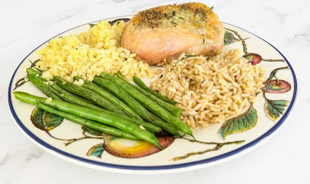 Herb butter chicken with brown rice, cauliflower rice and string beans on dinner plate.