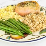 Herb butter roasted chicken with rice and string beans on a dinner plate