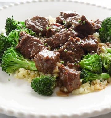Instant Pot Beef and Broccoli over Cauliflower rice on white plate
