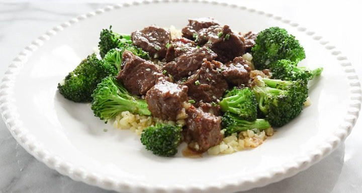 Beef and broccoli over cauliflower rice on white plate