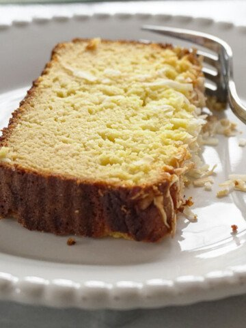 slice of low carb coconut pound cake on white plate