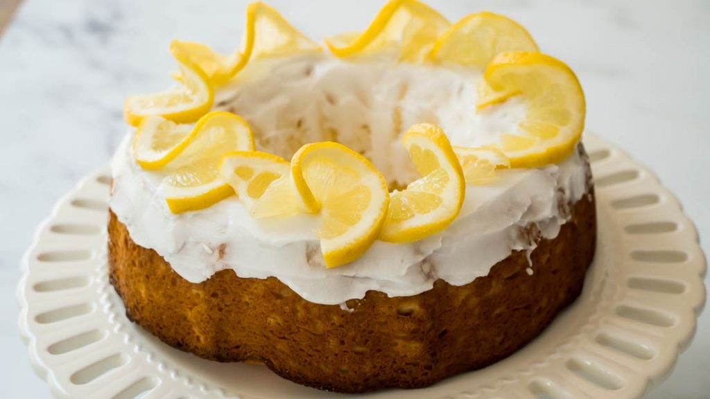 keto lemon yogurt cake with lemon slices and lemon glaze on white serving dish