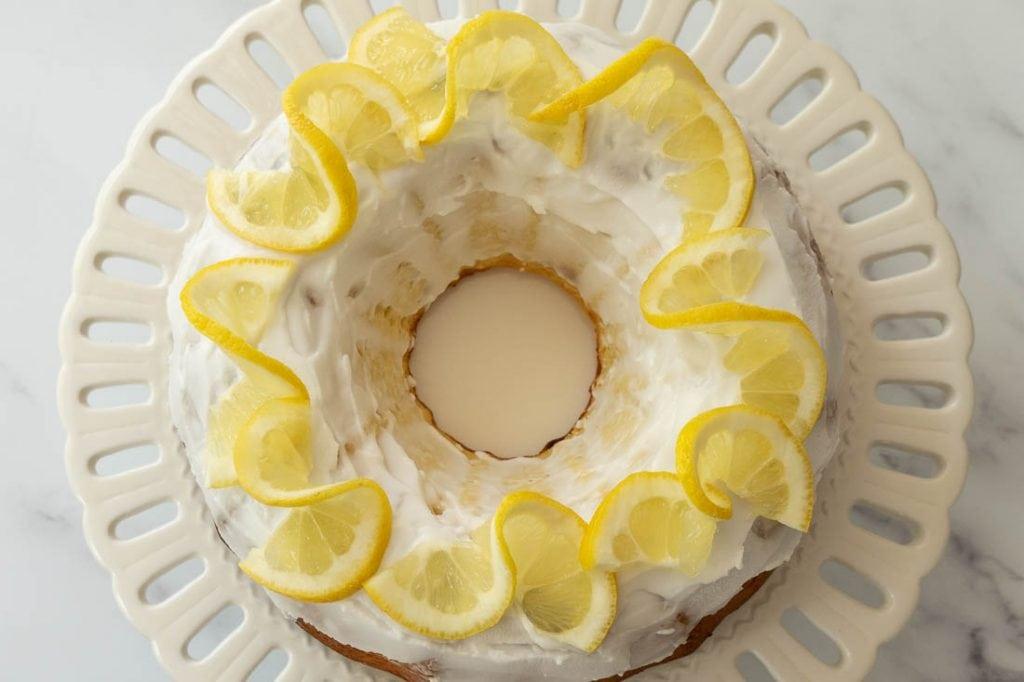 keto lemon yogurt cake with lemon glaze on white cake plate
