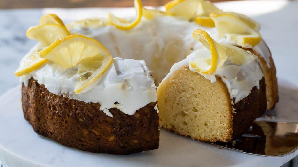 keto lemon yogurt cake with serving utensil on cake platter