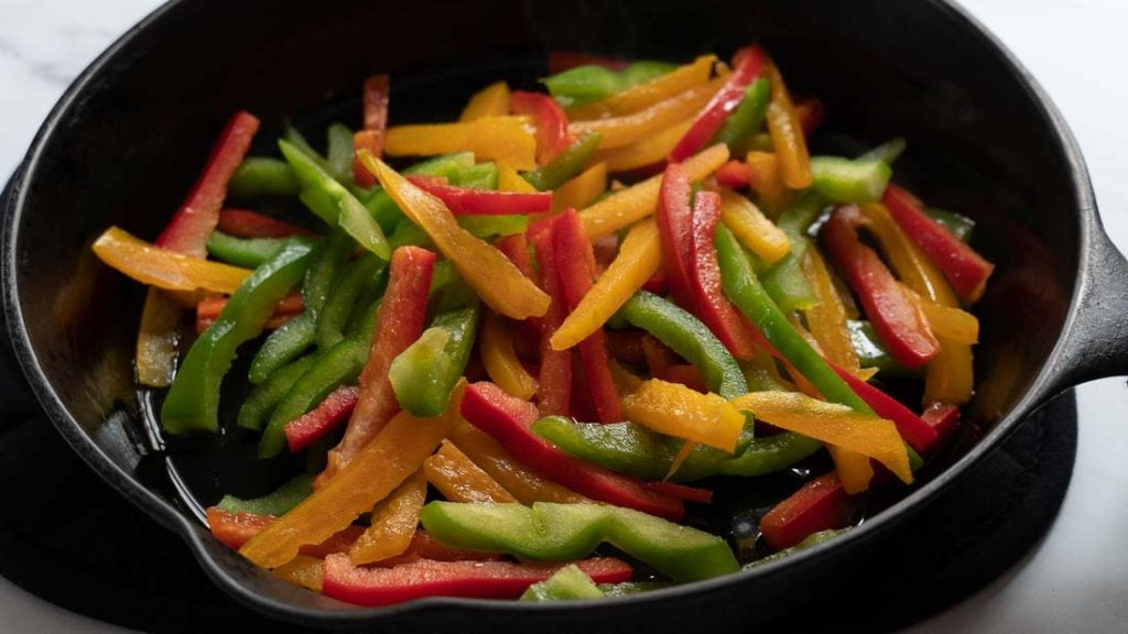 Tricolor peppers cooking in a cast iron skillet