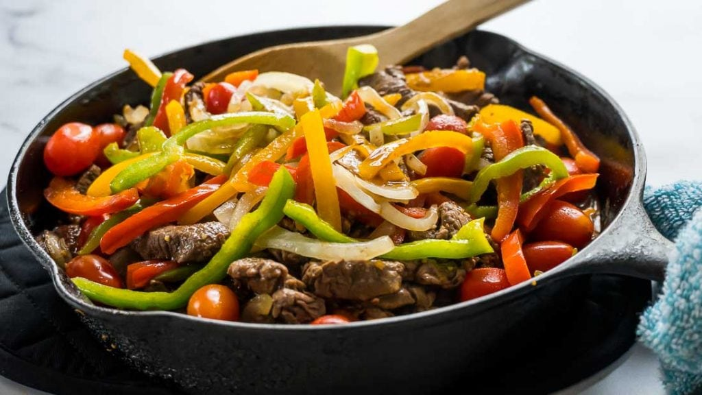 pepper steak with onions and cherry tomatoes in cast iron skillet
