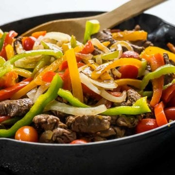 pepper steak and onions with tomatoes in a cast iron skillet