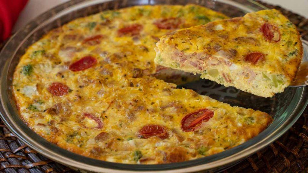 Serving slice of crustless broccoli and sun-dried tomato quiche in a pie plate.