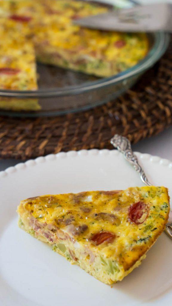 slice of crustless broccoli and sun dried tomato quiche on white plate