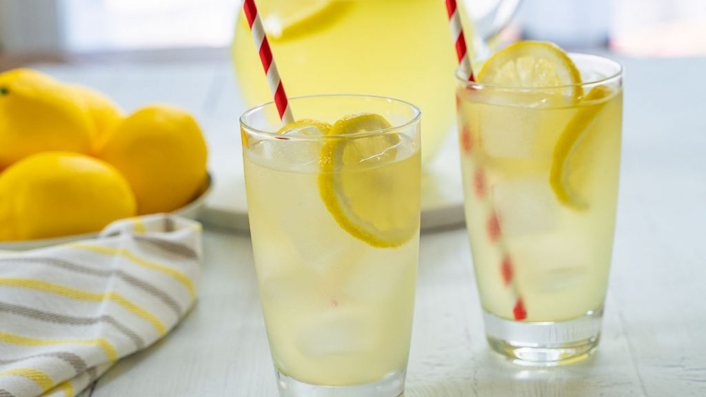 Glasses and a pitcher of keto lemonade, along with a bowl of lemons.