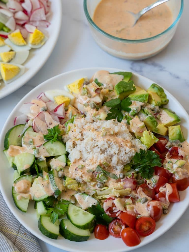 crab louie salad on plate with dressing in bowl