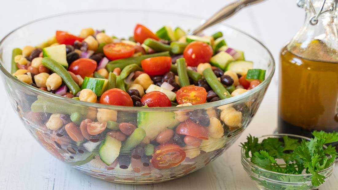 bean salad in glass bowl with dressing in decanter