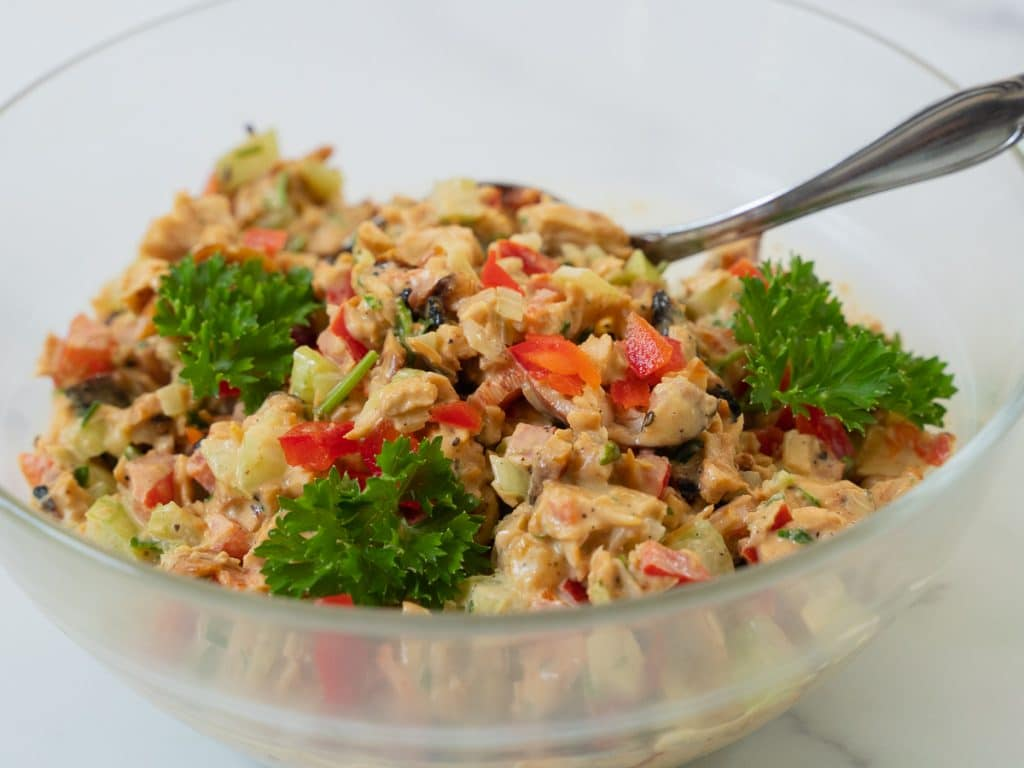 Chicken salad made with red peppers, celery, tarragon, chives and parsley in a glass bowl.