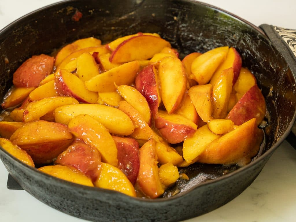 Sliced peaches in a cast iron skillet