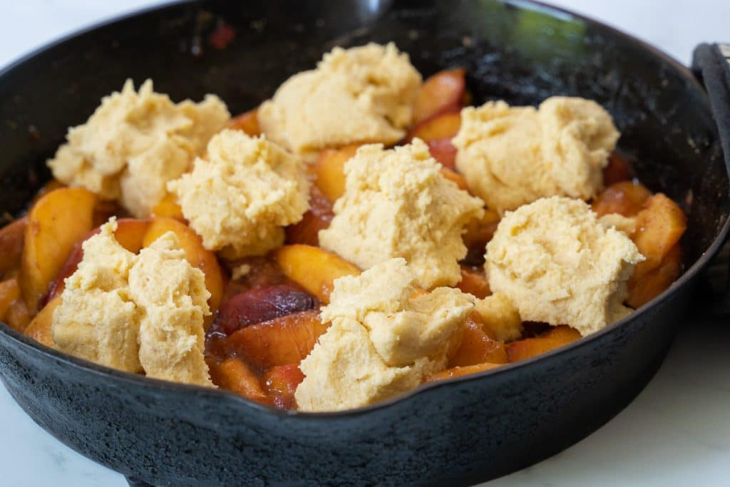 Sliced peaches and biscuit dough in a cast iron skillet