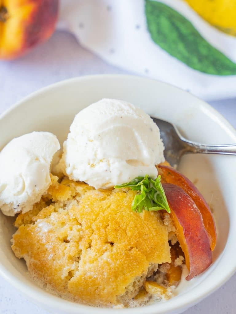 Keto peach cobbler with vanilla ice cream in a dish