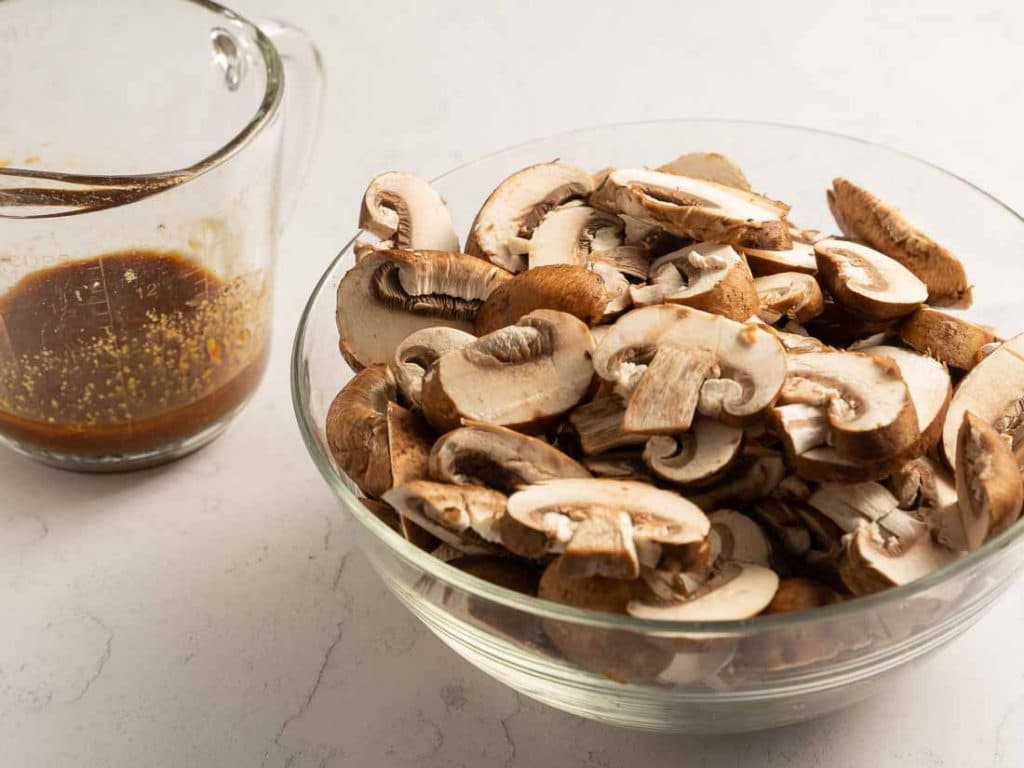 Marinade in a glass measureing cups and sliced mushrooms in a glass bowl