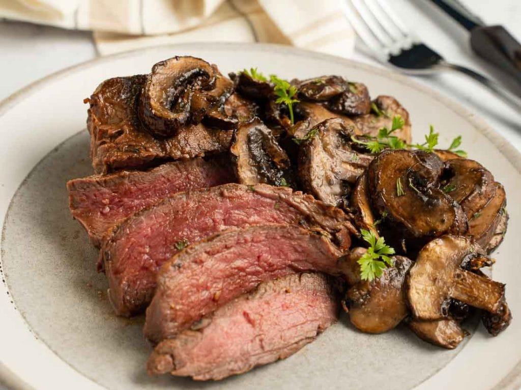 Slice filet steak with marinated, air fryer mushrooms on a beige dinner plate