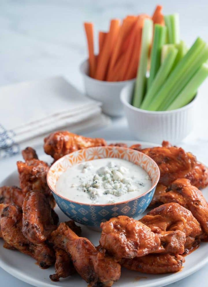keto buffalo chicken wings on plate with blue cheese dressing, celery and carrots