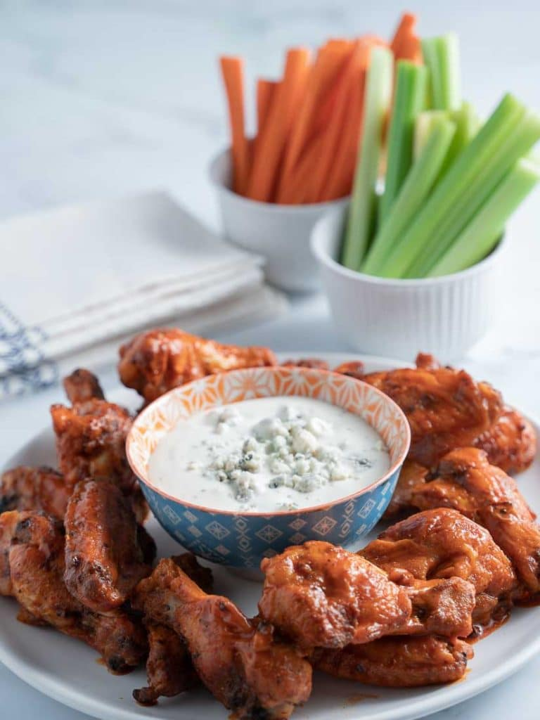 keto buffalo chicken wings on white plate with blue cheese dressing, carrots and celery