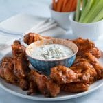 Keto Buffalo chicken wings on plate with carrots, celery, blue cheese dressing