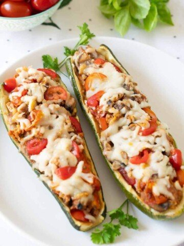sausage and mushroom zucchini boats on white plate