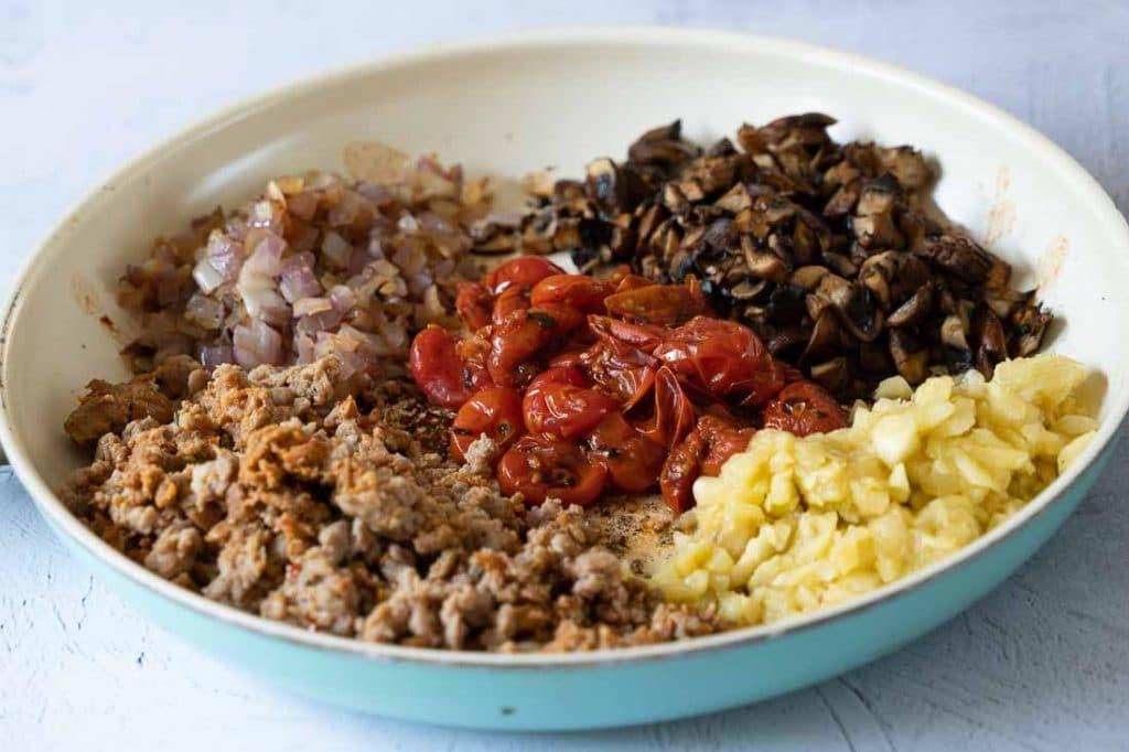 Onions, cherry tomatoes, mushrooms zucchini flesh, italian sausage in fry pan
