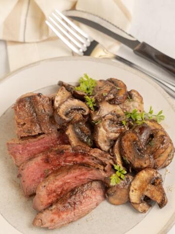 Marinated air fryer mushrooms and steak on beige plate