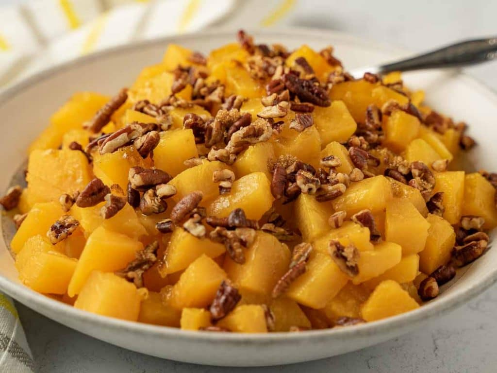 Cubed butternut squash and pecans in white bowl with spoon.