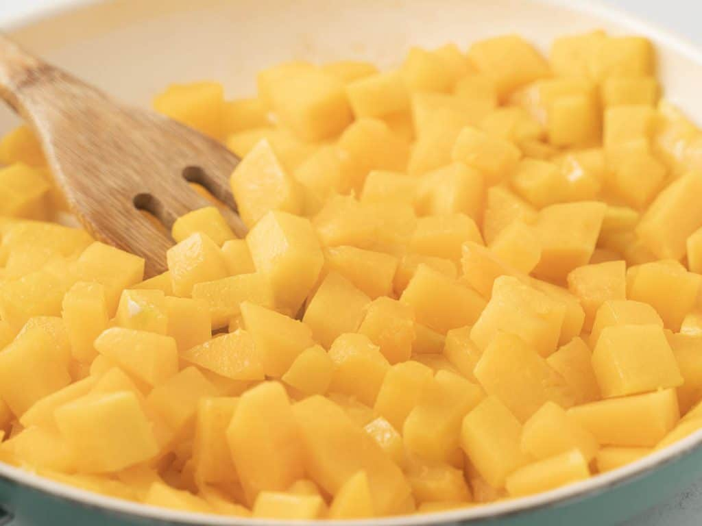 Cubed butternut squash in a saute pan with wooden spoon
