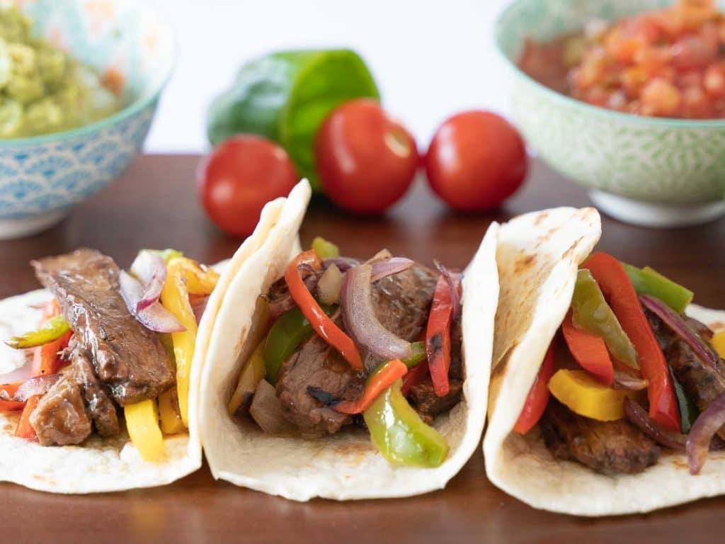 Instant pot steak fajitas in tortillas on wooden board.  Bowls of guacamole, salsa in small green and blue bowls.