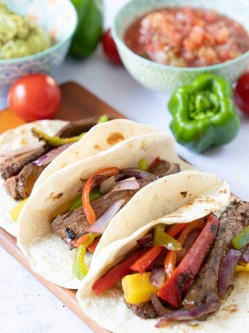 Instant pot steak fajitas on serving board with guacamole and salsa