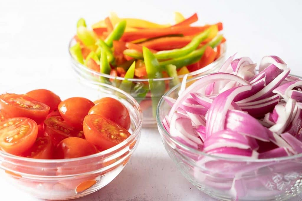 Sliced yellow, red, green peppers, cherry tomatoes and red onions.