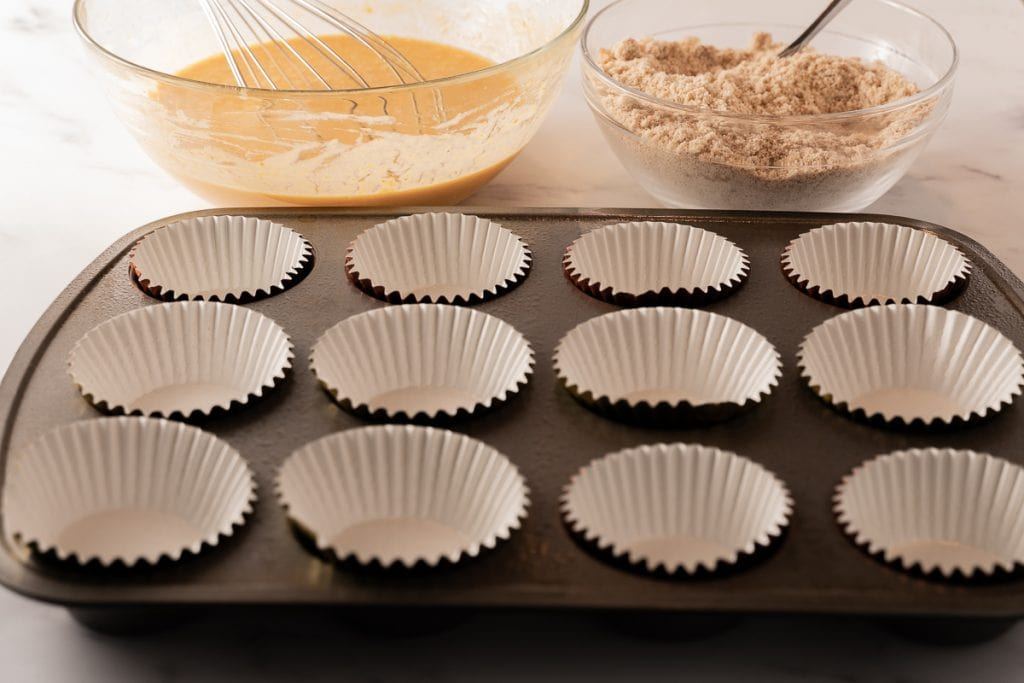 keto pumpkin muffin dry & liquid ingredients in glass bowl. paper liners in muffin pan.