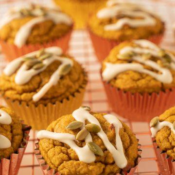 keto orange glazed pumpkin muffins with roasted pumpkin seeds on cooling rack