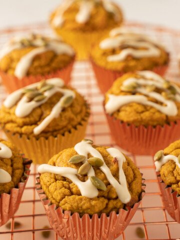 keto orange glazed pumpkin muffins with roasted pumpkin seeds on cooling rack