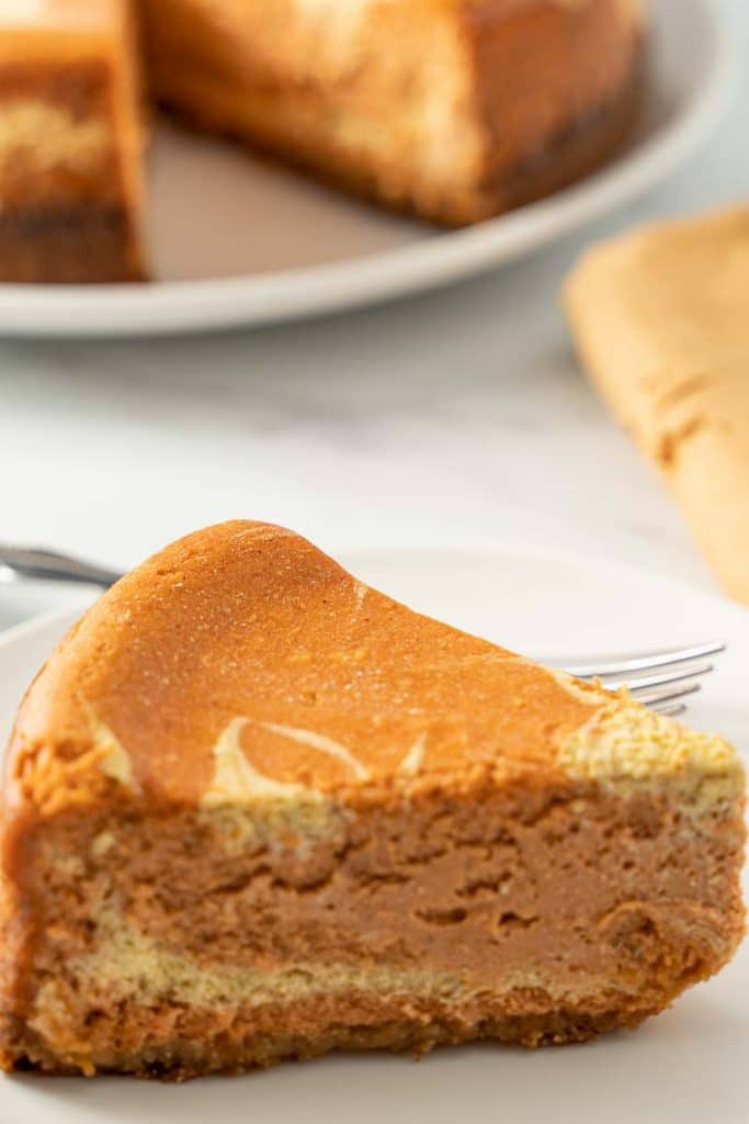 keto swirled pumpkin cheesecake on white plate with fork