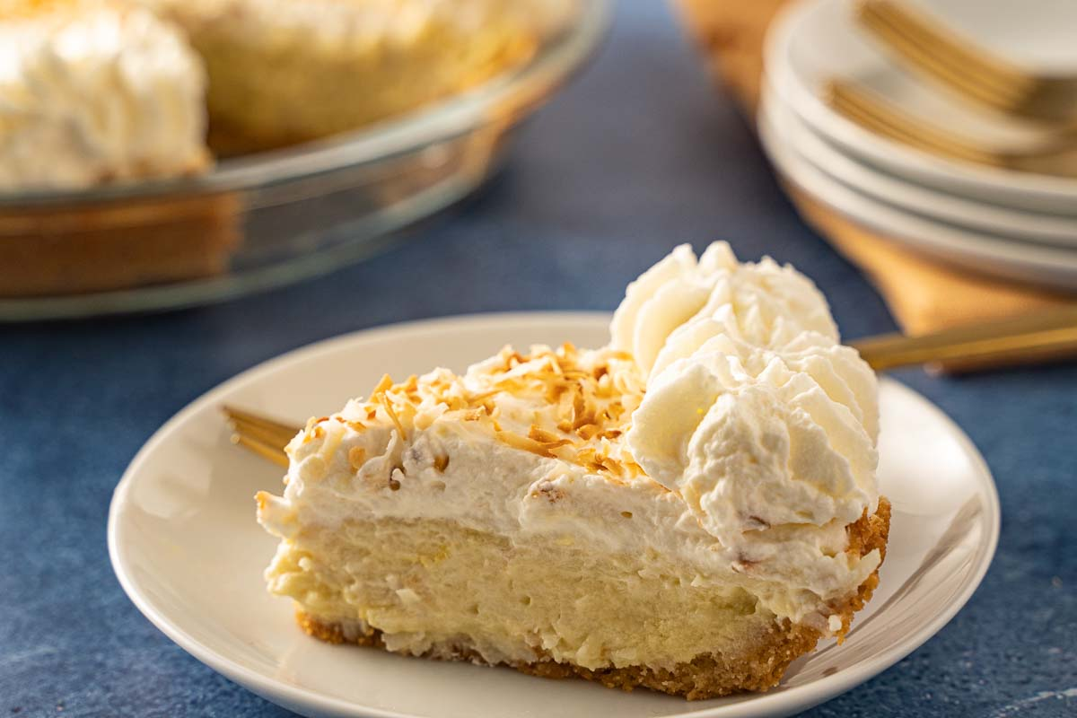 slice of keto coconut cream pie on white plate with gold fork