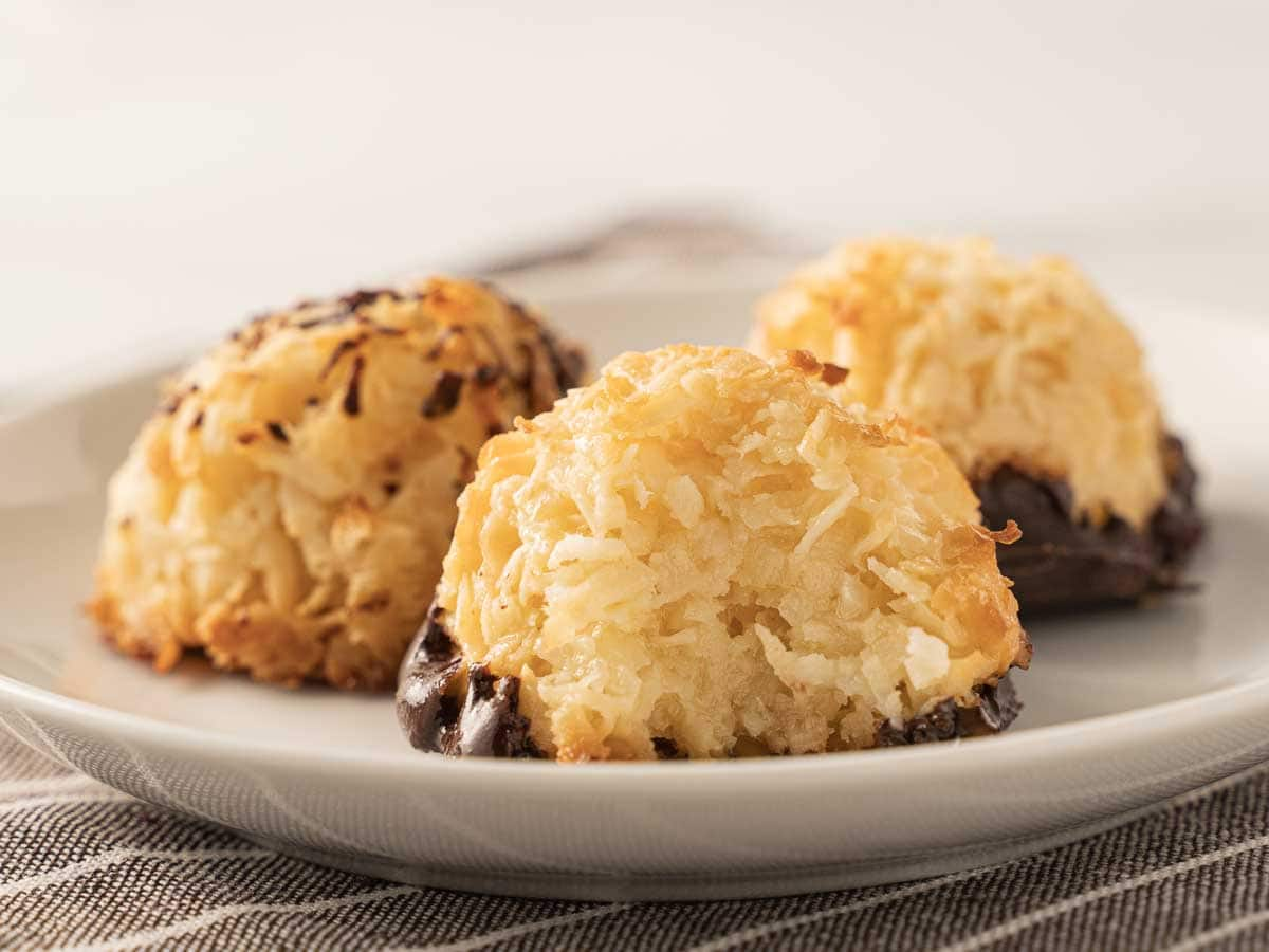 keto coconut macaroons, dipped in chocolate on a white plate