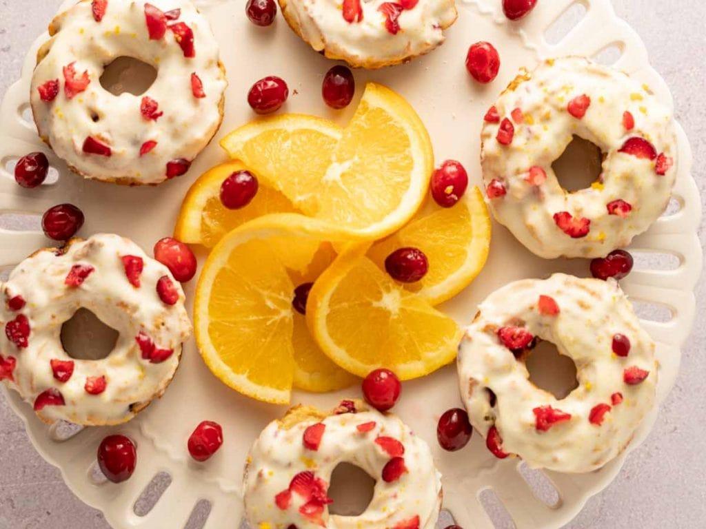 keto cranberry donuts with orange slice on white platter