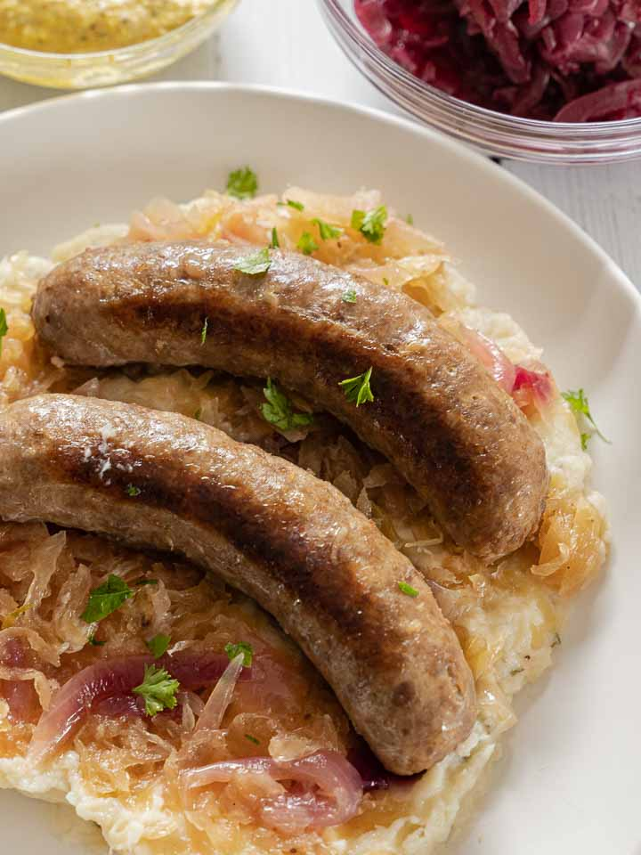 Instant pot brats with red onion, sauerkraut on mashed cauliflower