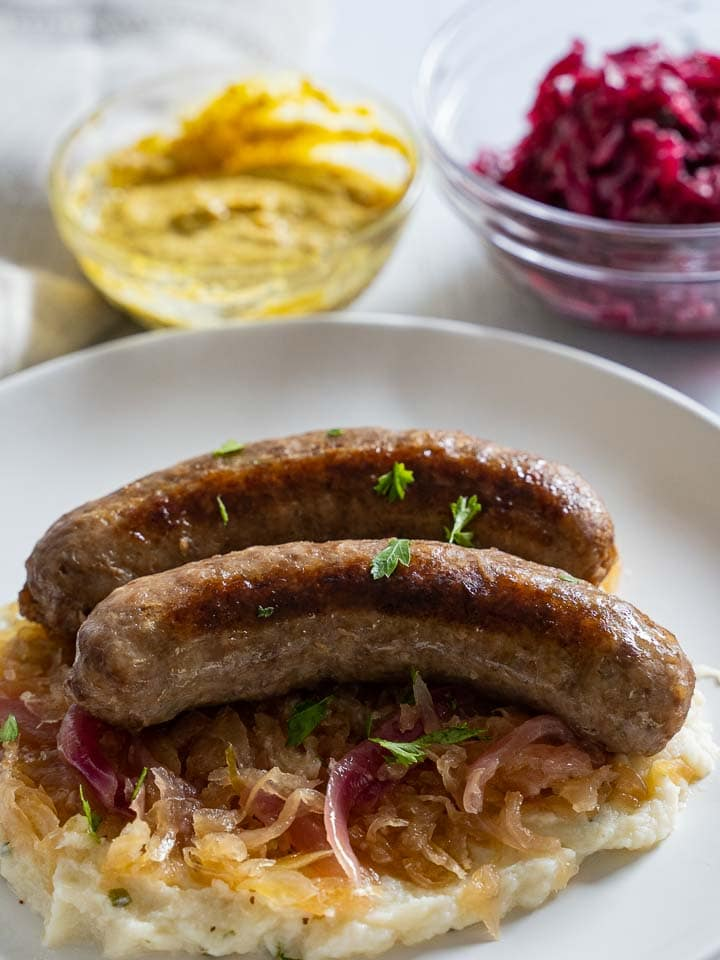 Instant pot brats, red onions, sauerkraut served on mashed cauliflower, mustard, red cabbage on white plate