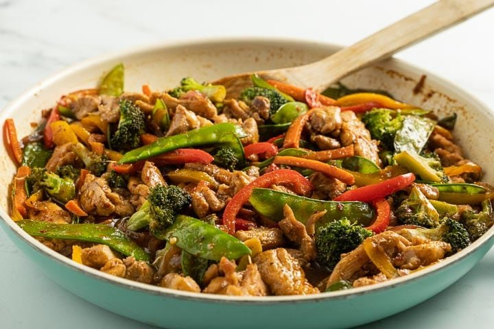 keto chicken stir fry in pan with wooden spoon